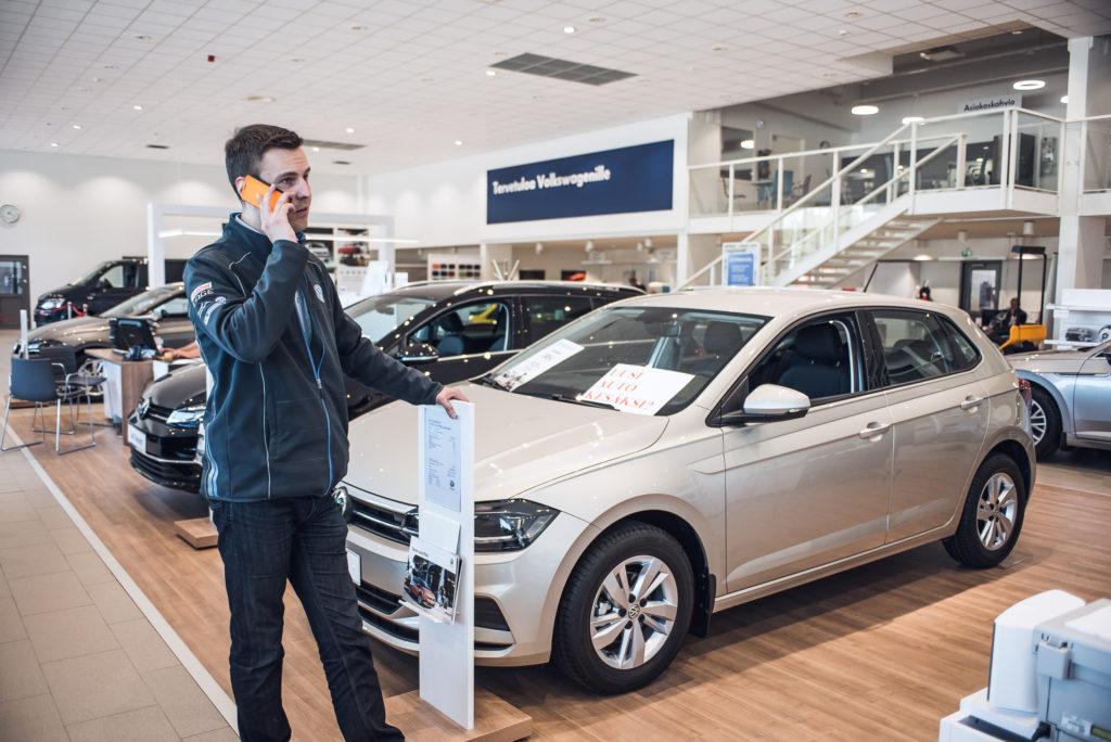 Automyyjä, Juha Sepponen, keskustelee asiakkaan kanssa puhelimessa Volkswagen showroomissa