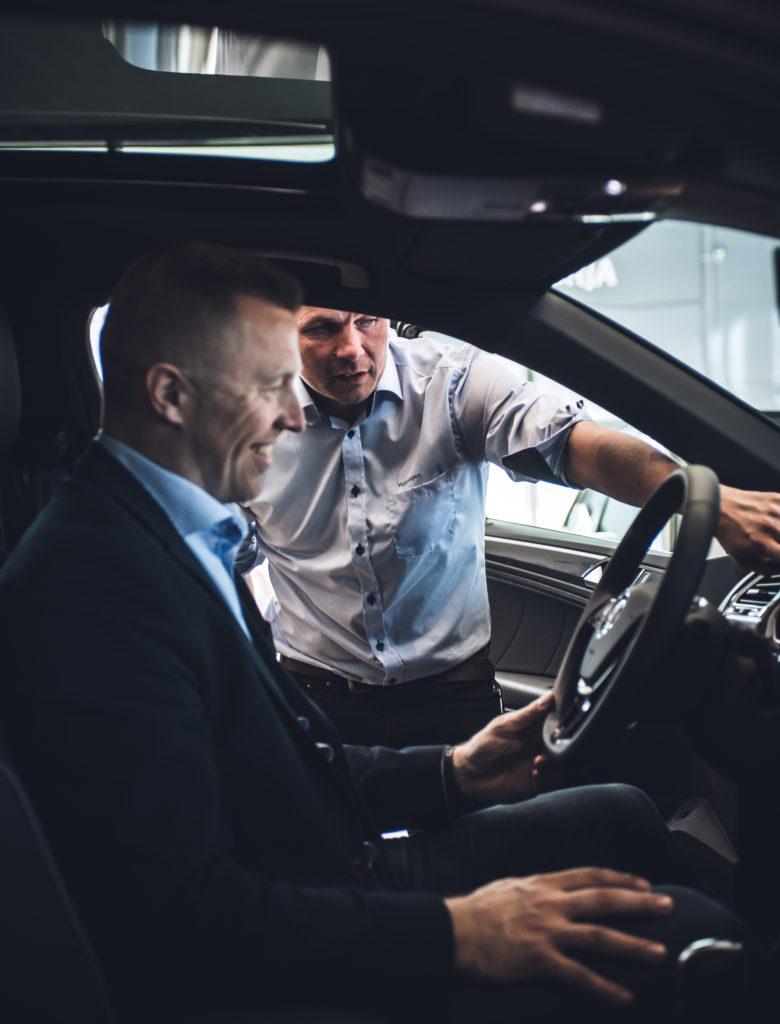 Seat myyjä luovuttamassa uutta autoa asiakkaalle