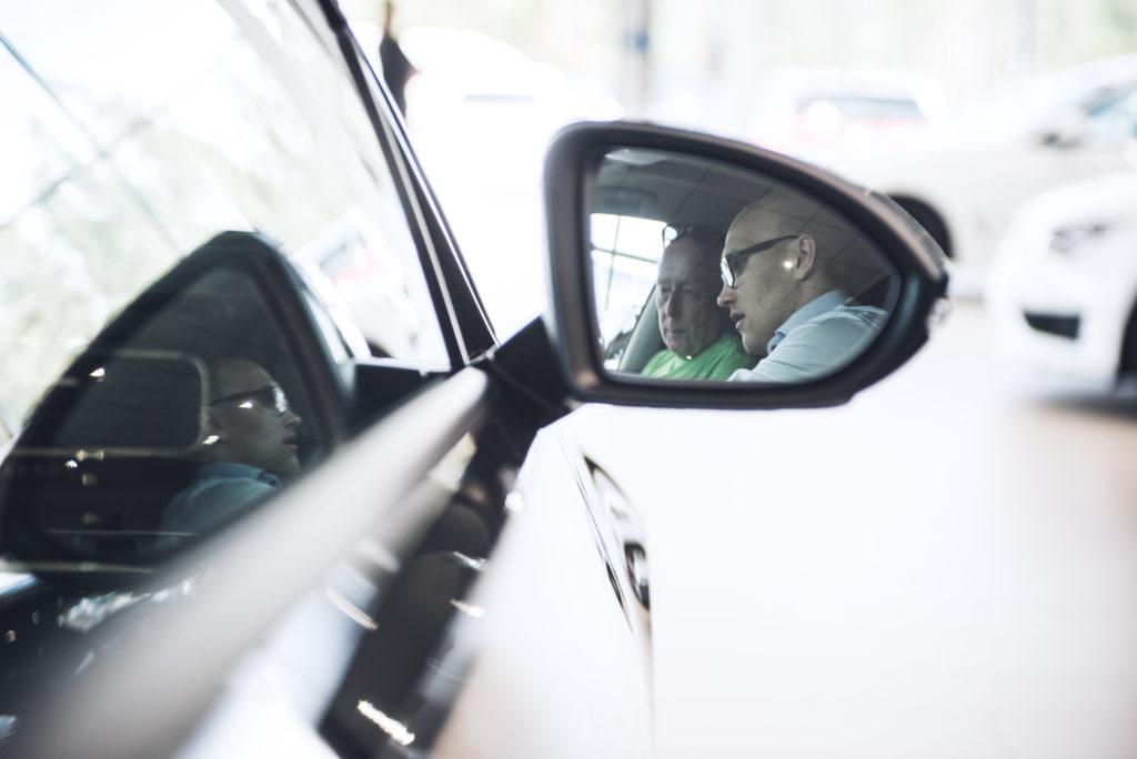 Liikkeen kauppias, Juhani Mattinen, luovuttamassa uutta autoa asiakkaalle