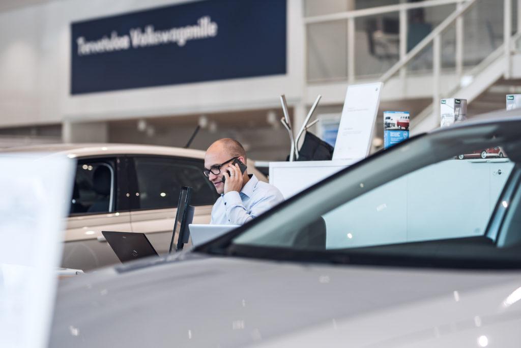 Myyjä puhuu puhelimessa auton takana