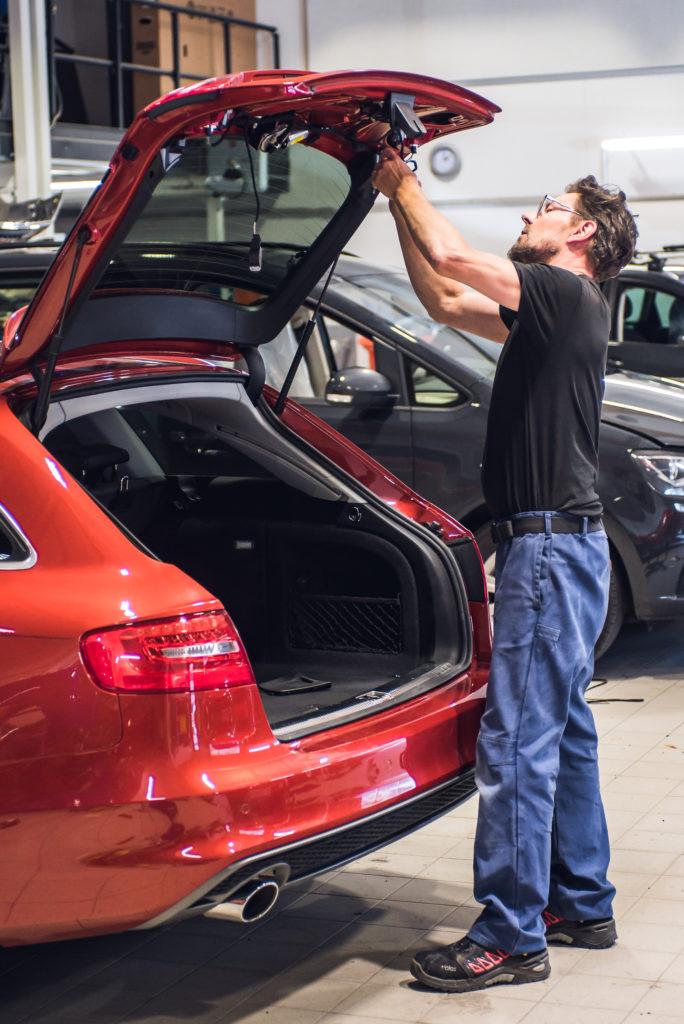 Autopeltiseppä, Juha Kairenius, asentaa takaluukun johdotuksia asiakkaan Audiin